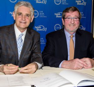 Bruce Stillman and Michael Dowling sign a ground-breaking accord.
